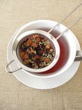 Herbal tea with fruits and flowers in tea strainer Royalty Free Stock Images