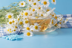Herbal tea in a glass cup, bouquet chamomiles. pills and thermom Stock Photo