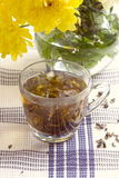 Herbal tea in glass cup and flowers Stock Image