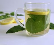 Herbal tea in a glass cup , fresh lemon balm leaves. The tea balm, the essential oil, and the extract are used in. Herbal tea in a glass cup , fresh lemon balm Stock Photo
