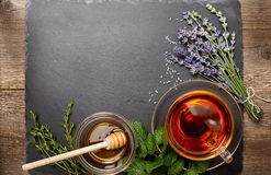 Herbal tea in a glass cup, honey. Different types of herbs: lavender, mint, thyme on black stone background (top view stock photos