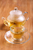 Herbal tea in the glass cup. And tea pot on wooden table stock images