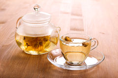 Herbal tea in the glass cup. And tea pot on wooden table royalty free stock images