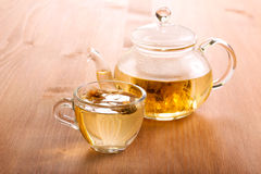Herbal tea in the glass cup. And tea pot on wooden table stock photos