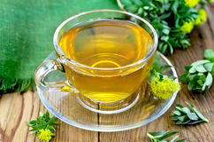 Herbal tea in a glass cup with Rhodiola rosea on the board Royalty Free Stock Photo