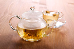 Herbal tea in the glass cup and tea pot. On wooden table stock photos