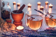 Herbal tea in a glass cups with lavender, beautiful light from candles royalty free stock photos