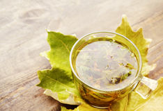 Herbal tea in a glass transparent cup on autumn leaves on a wooden table. Royalty Free Stock Images