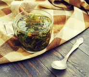 Herbal tea in a glass transparent cup on a wooden table. Royalty Free Stock Photo