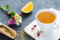 Herbal tea, green tea cup. Cup of herbal green tea, lemon wedge, dry herbal tea, rose buds and bouquet of flowers. Concept of antioxidant beverage, healthy stock photo