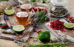 Herbal tea. With herbs and berries on a rustic wooden board royalty free stock photo