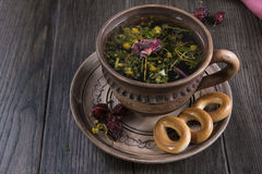Herbal tea, herbs and flowers in a  clay cup with cookie. On wooden table Stock Photography
