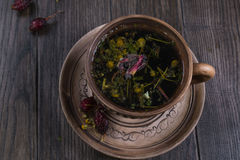 Herbal tea, herbs and flowers in a  clay cup on wooden table. Autumn Herbal tea with hip roses, chamomile, herbs on wooden table in a  clay cup Royalty Free Stock Image