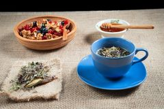 Real herbal tea in a blue Cup filled on a napkin, and honey in a bowl of honeycomb in a wooden bowl with red currants and blueber Royalty Free Stock Photography