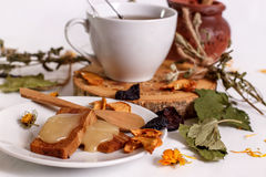 Herbal tea with honey, marshmallows and dried fruit. On a white table Stock Photo