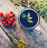 Herbal tea in an iron mug, red rosehip and St. John`s Wort flowers Royalty Free Stock Images