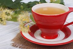 Herbal tea with lime in a red cup. On a wooden table stock images
