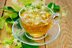 Herbal tea from linden flowers in a cup on the board Royalty Free Stock Images