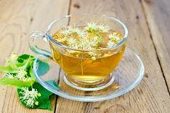 Herbal tea of linden flowers in glass cup on board Royalty Free Stock Image