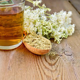 Herbal tea of meadowsweet dried in spoon and mug. Wooden spoon with dried flowers, a bouquet of fresh flowers of meadowsweet, tea in glass mug on the wooden Royalty Free Stock Image
