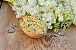 Herbal tea from meadowsweet dry on a spoon. Wooden spoon with dried flowers of meadowsweet, a bouquet of fresh flowers of meadowsweet against a wooden board Stock Photo