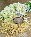 Herbal tea of meadowsweet in strainer on board. Metal sieve with dried flowers of meadowsweet, a bouquet of fresh flowers of meadowsweet on a wooden boards Stock Photo