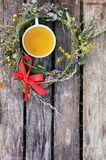 Herbal tea of medical plants in a cup outdoors on old weathered boards. Herbal tea of medical plants in a cup on weathered wooden boards outdoors stock photography