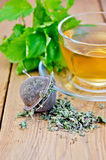 Herbal tea from melissa in cup with strainer on board Stock Photo