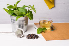 Herbal tea with melissa in a glass cup. A green napkin on a light green wooden table top royalty free stock photos