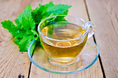 Herbal tea with melissa on a wooden board. Herbal tea in glass cup, fresh melissa leaves on the background of wooden boards Stock Image