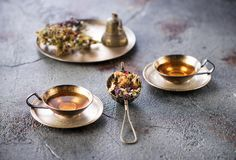 Herbal tea in metal cups and dried herbs. On a gray concrete background royalty free stock photo