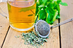 Herbal tea with mint in mug with strainer on board. Herbal tea in a glass mug, metal sieve with dry mint leaves, fresh mint leaves on a wooden boards background Stock Photos