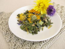 Herbal tea mix with flowers on a small plate. Herbal tea mix with flowers on a small white plate Royalty Free Stock Photography