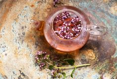 Herbal tea with oregano in a glass teapot on vintage background, top view. Herbal tea with oregano in a glass teapot stock photography