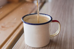 Herbal tea is poured into an enameled mug on a wooden background in the kitchen and drops of tea fly. Royalty Free Stock Photos
