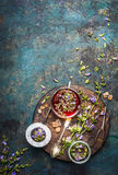 Herbal tea preparation with fresh healing herbs and flowers on dark rustic background Stock Images