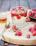 Herbal tea with rose buds and fresh raspberry. Herbal tea with rose buds and fresh raspberry on a wooden cutting board Royalty Free Stock Photography