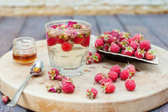 Herbal tea with rose buds and fresh raspberry. Stock Photography