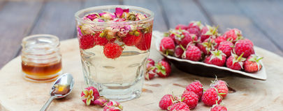 Herbal tea with rose buds and fresh raspberry. Stock Photo