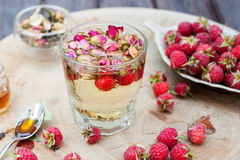 Herbal tea with rose buds and fresh raspberry. Stock Photos