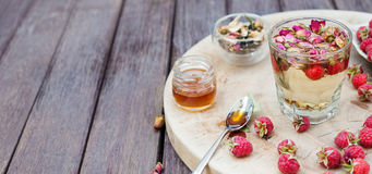 Herbal tea with rose buds and fresh raspberry. Herbal tea with rose buds and fresh raspberry on a wooden cutting board Royalty Free Stock Images