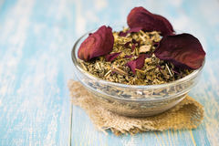 Herbal tea with rose petals on a rustic table. Drink Alternative Medicine. Royalty Free Stock Photo
