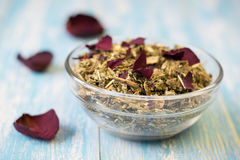 Herbal tea with rose petals on a rustic table. Royalty Free Stock Image