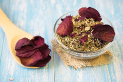 Herbal tea with rose petals on a rustic table. Stock Photography