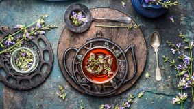Herbal tea setting with cup of herbal tea, herbs and flowers. Vintage tea set on dark rustic background, top view. Healthy ,healing or detox drinks concept royalty free stock images