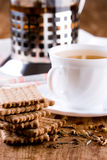 Herbal tea and some fresh cookies. Cup of herbal tea and some fresh cookies closeup on wooden table Royalty Free Stock Image