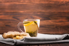 Herbal tea. Sweet lemon tea and a cut ginger on a wooden background. A cup of ginger tea. Natural and hot drinks for breakfast. Royalty Free Stock Photography