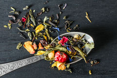 Herbal tea in a teaspoon. Aromatic herbal tea in a teaspoon on a black wooden background Stock Images