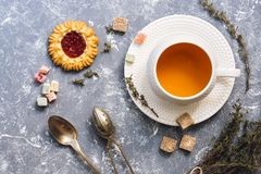 Herbal tea with thyme with sweets on a gray background, top view. Flat lay.  Stock Images