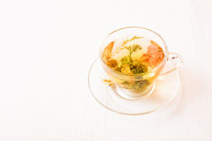 Herbal tea in a transparent cup. On white table stock photo